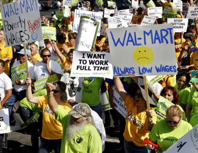 Image: Striking Walmart workers gather during a rally to protest unsafe working conditions and poor wages outside a Walmart store in Pico Rivera
