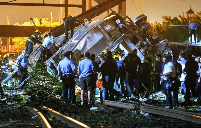 Rescue workers climb into the wreckage of a crashed Amtrak train in Philadelphia, Pennsylvania May 12, 2015. The Amtrak passenger train with more than 200 passengers on board derailed in north Philadelphia on Tuesday night, killing at least five people and injuring more than 50 others, several of them critically, authorities said. Authorities said they had no idea what caused the train wreck, which left some demolished rail cars strewn upside down and on their sides in the city's Port Richmond neighborhood along the Delaware River.  REUTERS/Bryan Woolston      TPX IMAGES OF THE DAY